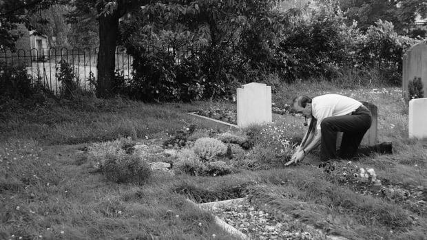Roald Dahl smokes a pipe as he uses a pair of garden shears to tend to a grave
