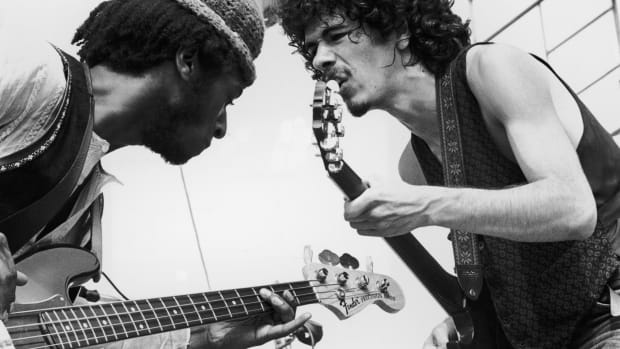Carlos Santana (right) and bassist David Brown perform with the group Santana at the Woodstock Music Festival in Bethel, New York
