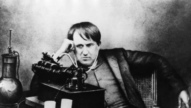 Thomas Edison listening to a phonograph through a primitive headphone