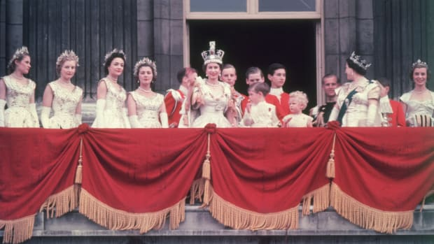 8_he newly crowned Queen Elizabeth II waves to the crowd from the balcony at Buckingham Palace. Her children Prince Charles and Princess Anne stand with her. (Photo by Hulton Archive:Getty Images)