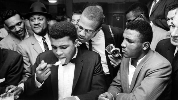 Malcolm X (C), standing behind tux-clad Muhammad Ali (L), who is surrounded by jubilant fans after he beat Sonny Liston for the heavyweight championship of the world.