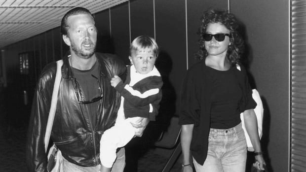 Eric Clapton singer songwriter and girlfriend Lori Del Santo walk through airport with son Conor