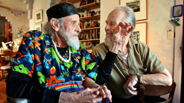 Harry Hay (L) brushes the cheek of his partner John Burnside at their home in San Francisco, July 2002
