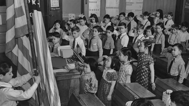 A group of children saluting the American flag at a school in the Chinatown area of Manhattan circa 1960