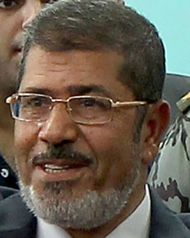 RECROPPED VERSIONMuslim Brotherhood candidate Mohammed Mursi waves after casting his ballot at a polling station in the city of Zagazig, 90 kms north of Cairo in the eastern part of the Nile Delta, on June 16, 2012 as Egyptians voted in a divisive presidential runoff pitting him against ousted strongman Hosni Mubarak's last premier Ahmed Shafiq, two days after the top court ordered parliament dissolved. AFP PHOTO/MARWAN NAAMANI        (Photo credit should read MARWAN NAAMANI/AFP/GettyImages)