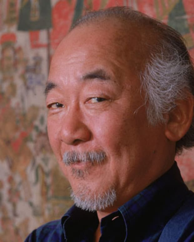 Portrait of American actor Pat Morita standing against a tapestry, 1988. (Photo by Nancy R. Schiff/Getty Images)