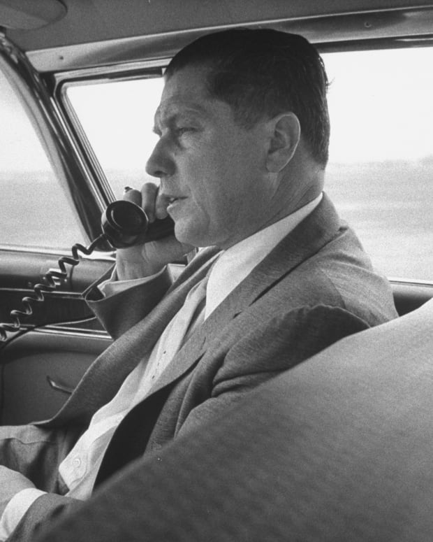 Teamsters boss Jimmy Hoffa using a telephone in the front seat of his chauffeured car
