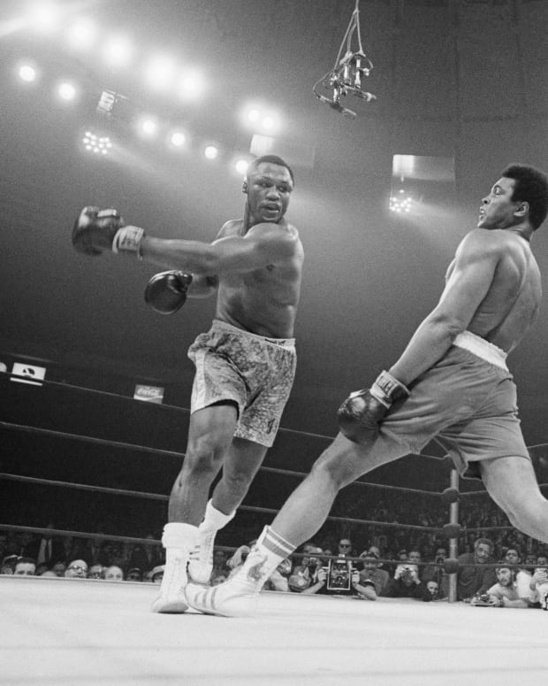 Boxer Muhammad Ali steps away from a punch thrown by boxer Joe Frazier during their heavyweight title fight at Madison Square Garden in 1971