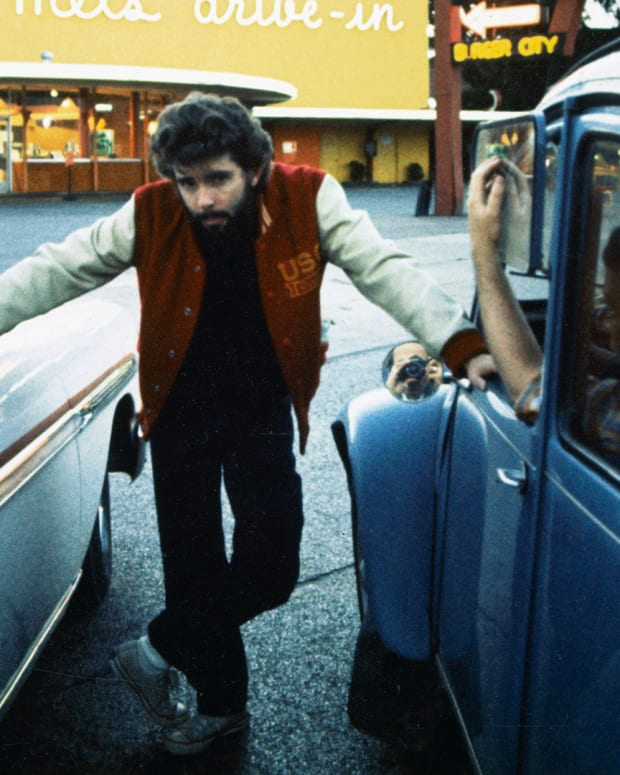 George Lucas posing between two cars