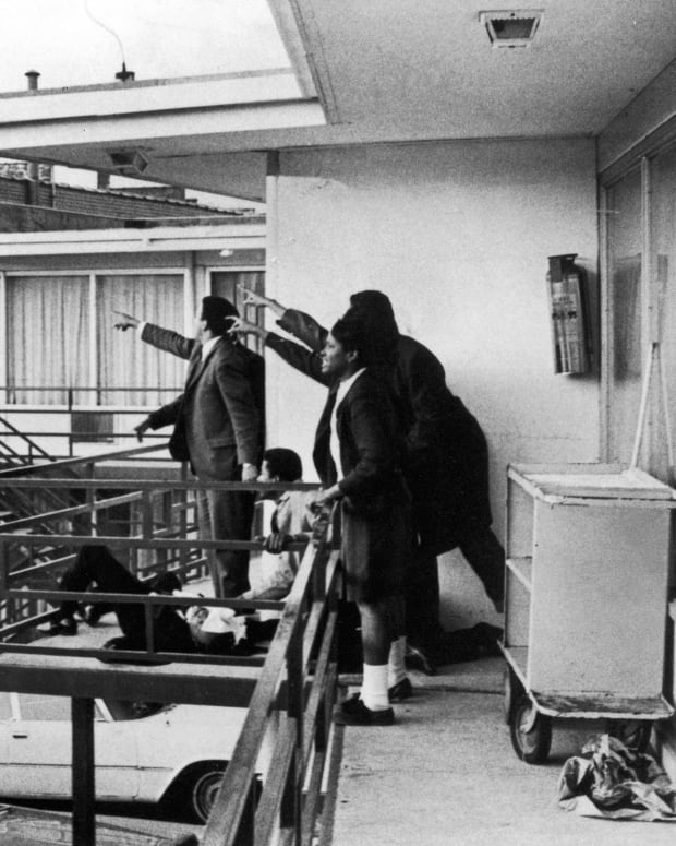 Andrew Young and others standing on balcony of Lorraine Motel pointing in direction of assailant after assassination of civil rights leader Martin Luther King Jr., who is lying at their feet.
