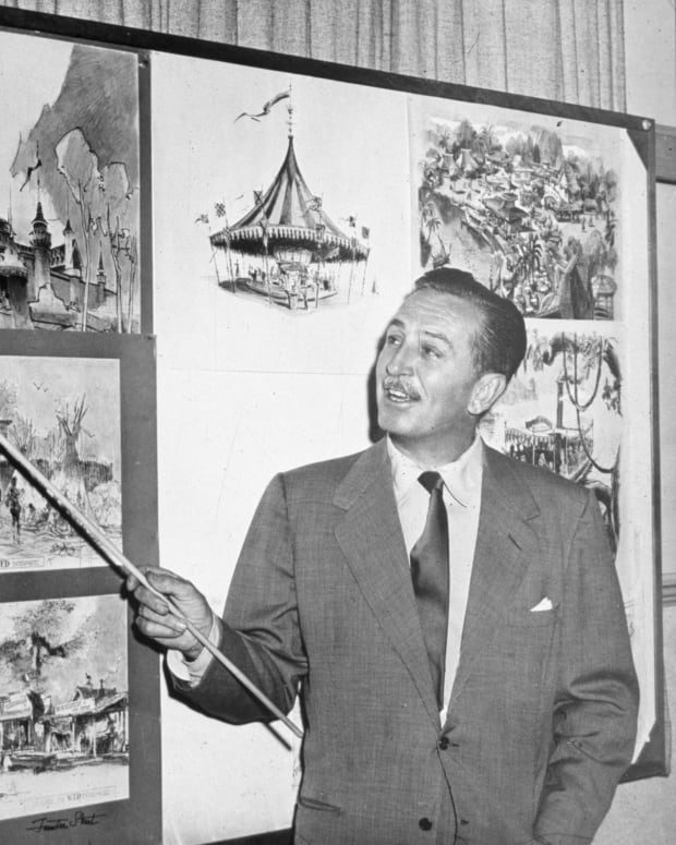 American producer, director, and animator Walt Disney uses a baton to point to sketches of Disneyland
