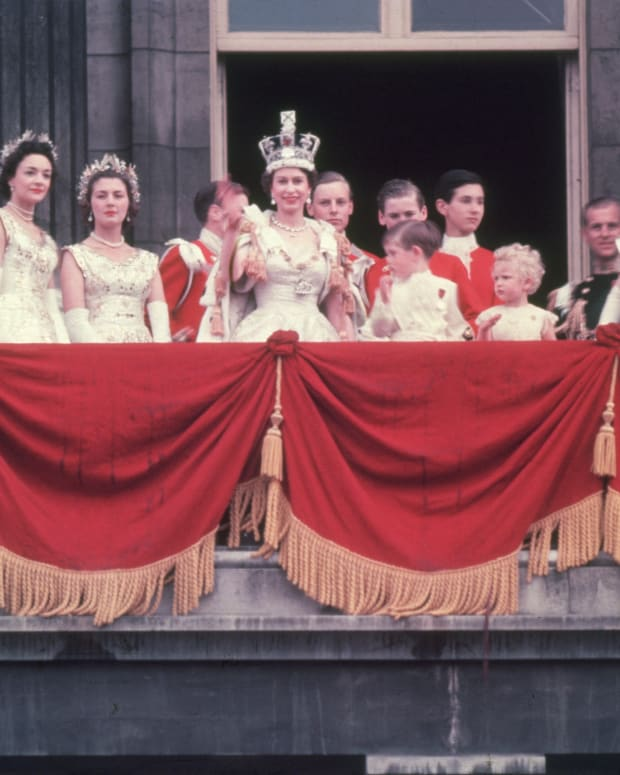 The newly-crowned Queen Elizabeth II waves to onlookers from the Balcony of Buckingham Palace alongside her children, Prince Charles and Princess Anne.