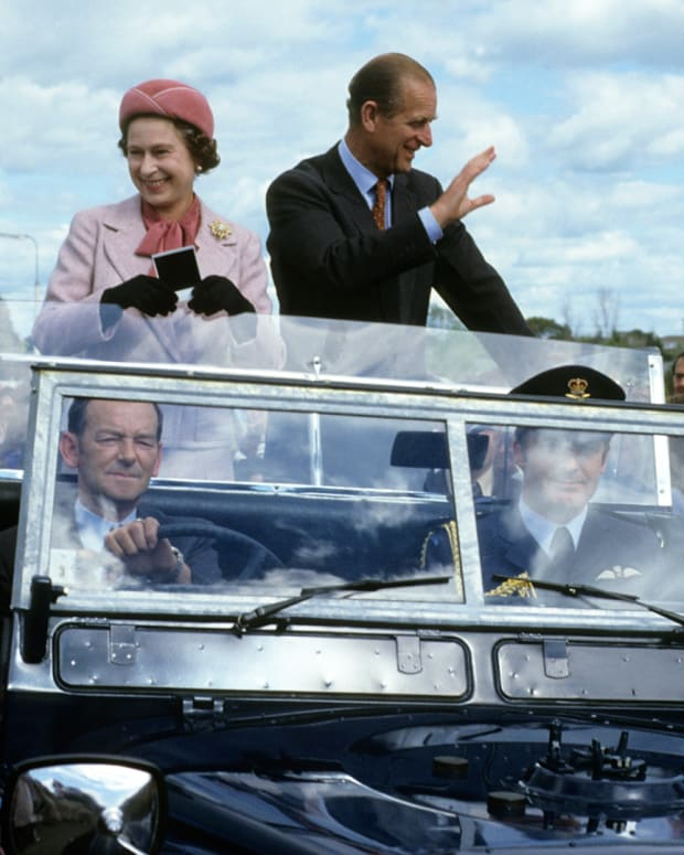 Queen Elizabeth ll and Prince Philip wave to well-wishers from their open car in October 1981 in Wellington, New Zealand
