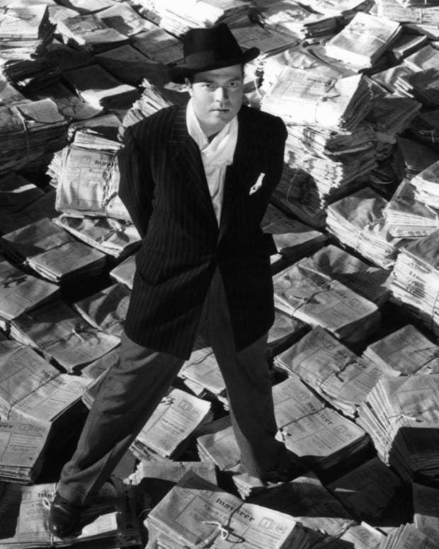 Orson Welles standing on stacks of newspapers in a scene from the film 'Citizen Kane'
