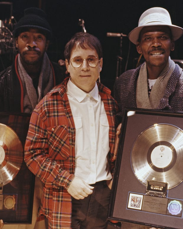 Paul Simon with four musicians, all holding gold discs of Paul Simon's album Graceland, on which they contributed, London, 1987