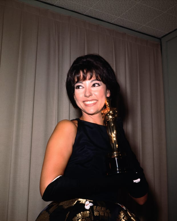 Rita Moreno smiling as she holds her Academy Award