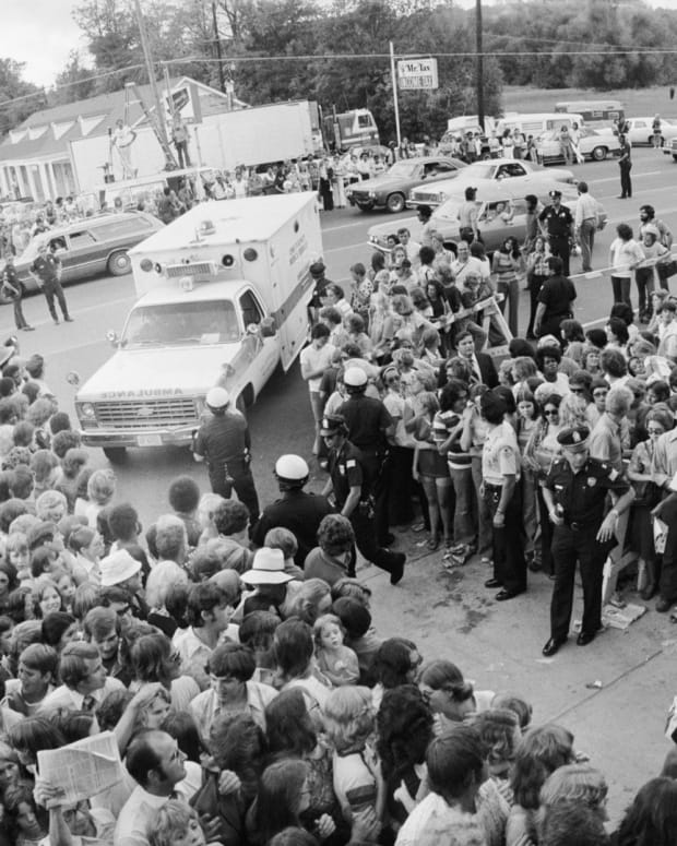 A crowd gathers outside the gates of Graceland, for the funeral of Elvis Presley.