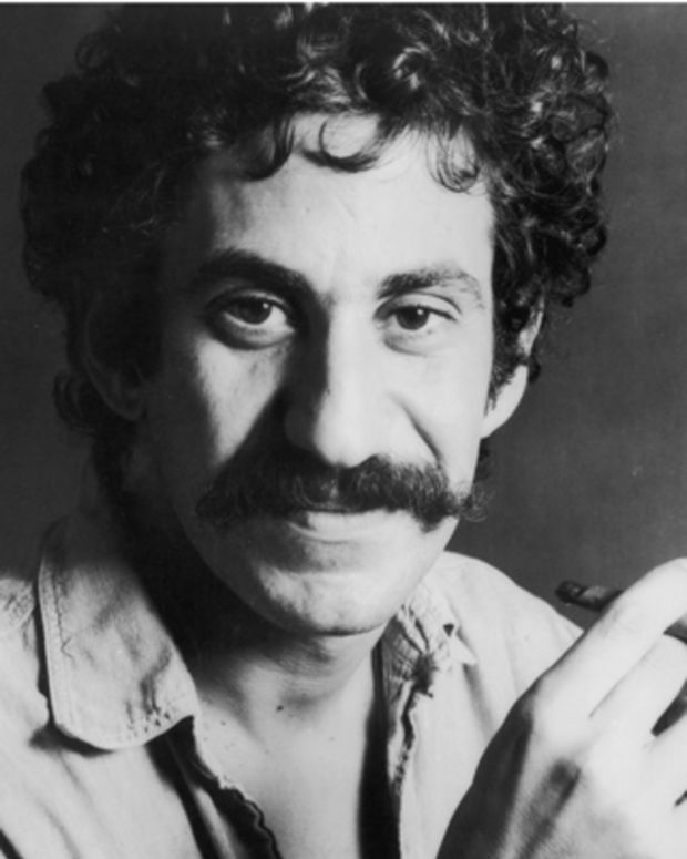 Headshot portrait of American singer-songwriter Jim Croce holding a cigar. His denim shirt is unbuttoned to reveal a tattoo and a chain with a bull's horn ornament.   (Photo by Hulton Archive/Getty Images)