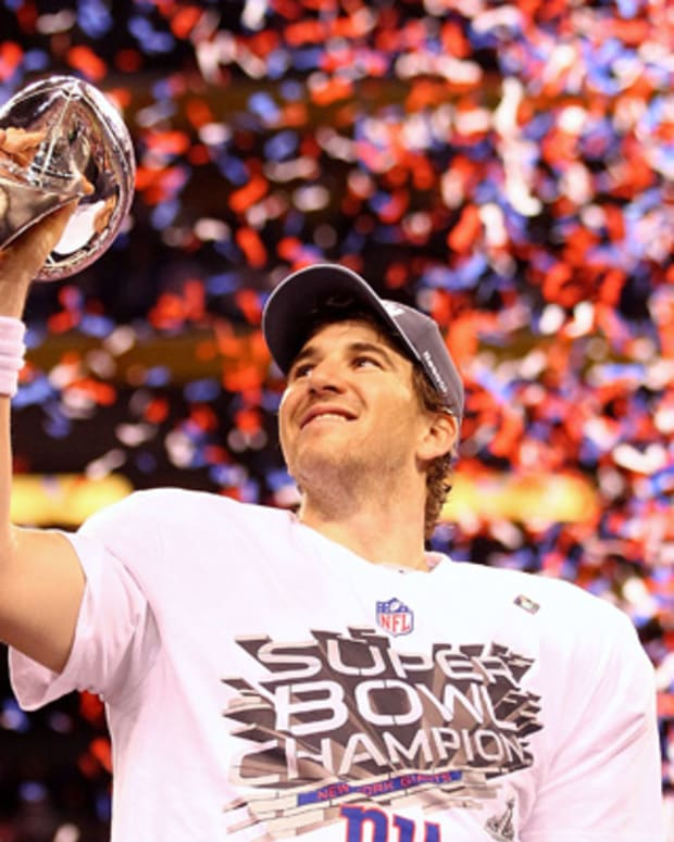 INDIANAPOLIS, IN - FEBRUARY 05:  Eli Manning #10 of the New York Giants hoist the Vince Lombardi Trophy after defeating the New England Patriots in Super Bowl XLVI at Lucas Oil Stadium on February 5, 2012 in Indianapolis, Indiana. The New York Giants defeated the New England Patriots 21-17.  (Photo by Al Bello/Getty Images)