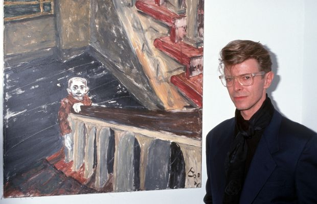 David Bowie: A musician, actor and artist, David Bowie stands next toone of his paintingsat a New York gallery show in1990. (Photo by Ron Galella/WireImage)