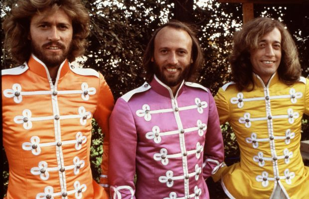 Bee Gees: Poor Maurice had to get the pink suit. The Bee Gees strike a pose on the set of Sgt. Pepper's Lonely Hearts Club Band (1978), a musical film directed by Michael Schultz. Left to right: Barry, Maurice and Robin Gibb.