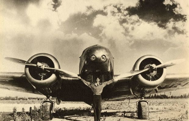Amelia Earhart: Amelia Earhart with arms spread in front of her plane, ca. February 12, 1937. George Palmer Putnam Collection of Amelia Earhart Papers, Courtesy of Purdue University Libraries, Karnes Archives and Special Collections.