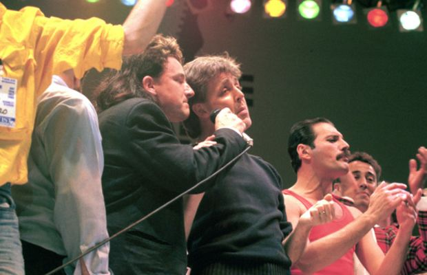 Freddie Mercury: Charitable Champions (Of The World): Bono (from left), Paul McCartney and Freddie Mercury perform together at the Live Aid Concert—a concerted effort to help end hunger in Ethiopia—on July 13, 1985, at London's Wembley Stadium.  (Photo by Steve Rapport/Photoshot/Getty Images.)