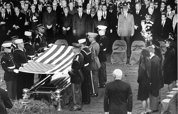 The honor guard drapes a flag over President Kennedy's casket at Arlington Cemetery. (Getty/National Archives)