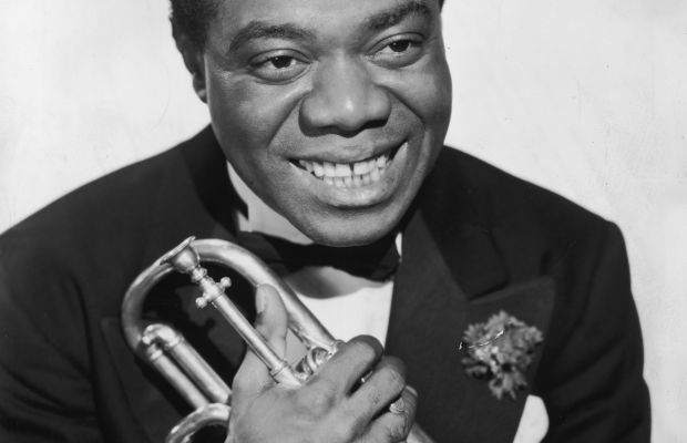 Gap-Toothed Grinners: circa 1945:  Headshot portrait of American jazz musician Louis Armstrong (1901 - 1971) smiling and holding a cornet against his chest. He is wearing a jacket and a bow tie.  (Photo by Hulton Archive/Getty Images)