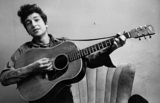 Folk Singers and Folk Revolutionaries: Bob Dylan poses for a portrait with his a Gibson acoustic guitar in New York City, in September 1961. The guitar, a Gibson model J50, was used on the album The Freewheelin' Bob Dylan (1963), which included the songs 'Girl from the North Country,' 'Masters of War' and 'A Hard Rain's a-Gonna Fall.' (Photo by Michael Ochs Archives/Getty Images.)