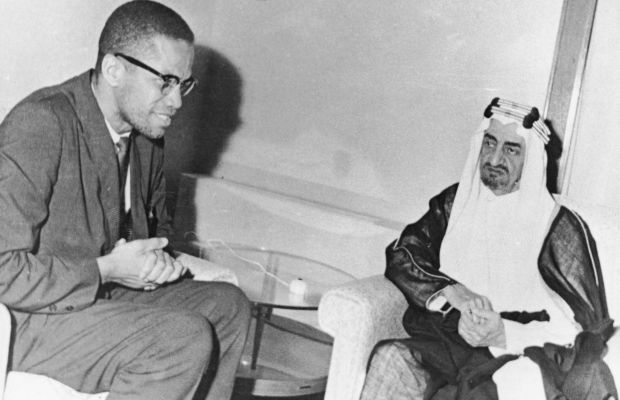 Malcolm X: Malcolm X sitis down with Prince (later King) Faisal al-Saud, the regent of Saudi Arabia, during a pilgrimage to the Muslim holy city of Mecca in April 1964. (Photo by Pictorial Parade/Getty Images)