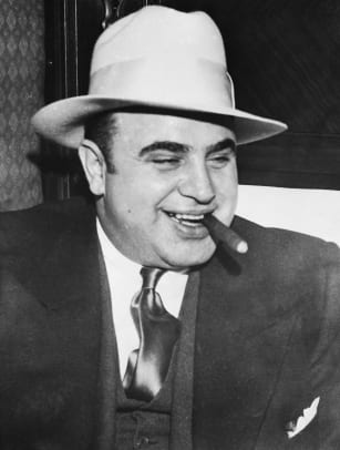 Al Capone smokes a cigar on the train carrying him to the federal penitentiary in Atlanta where he will start serving an eleven-year sentence.