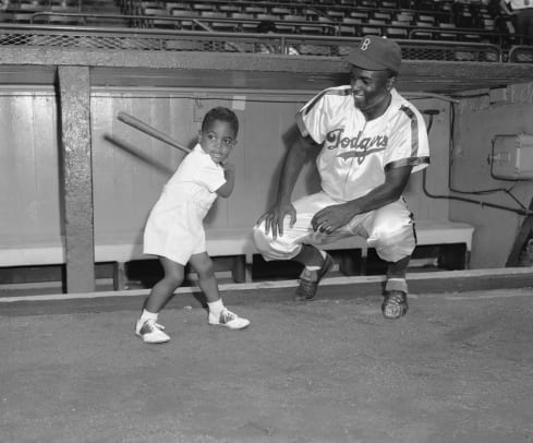 1_This intimate family picture was taken at Ebbets Field just before Jackie Robinson, Sr., joined his Brooklyn teammates in their contest against the Philadelphia Phillies tonight._Getty