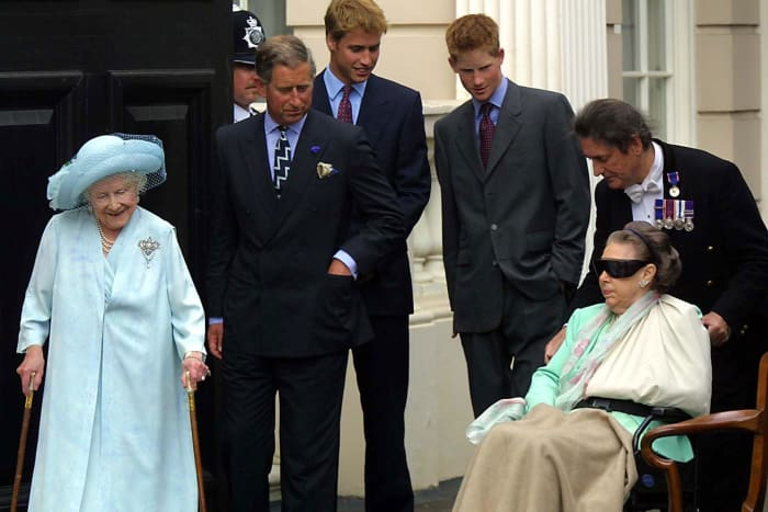 The Queen Mother (L) watches Princess Margaret being wheeled out by William Tallon (R) as Prince Charles, Prince William and Prince Harry look on at the Queen Mother's 101st birthday at Clarence House in London on August 4, 2001
