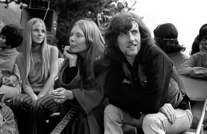 Joni Mitchell (C) and Graham Nash (R) wait before performing at the Big Sur Folk Festival at the Esalen Institue on September 14-15, 1969