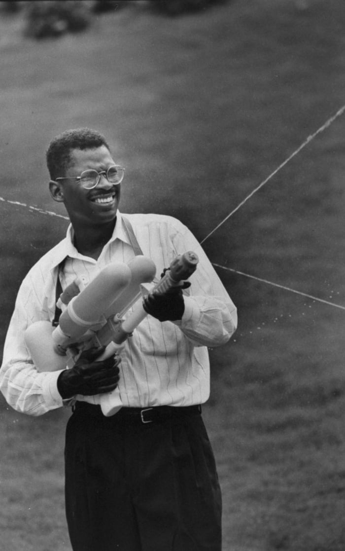 Lonnie Johnson firing a Super Soaker while standing on grass outside his home, June 1992