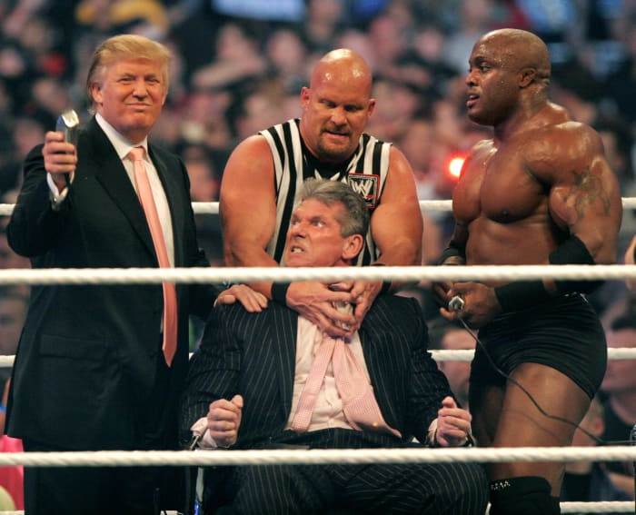 Vince McMahon (C) prepares to have his head shaved by Donald Trump (L) and Bobby Lashley (R) while being held down by ''Stone Cold'' Steve Austin after losing a bet in the