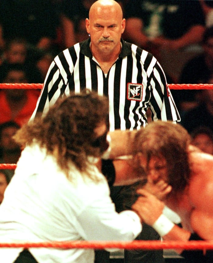 Jesse Ventura (C) watches as wrestlers Mick Foley (L) and Triple H (R) fight during SummerSlam Sunday night August 22, 1999, at the Target Center in Minneapolis, Minnesota