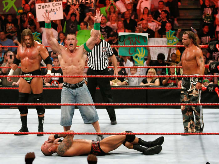 Triple H, John Cena and Shawn Michaels celebrate as wrestler Randy Orton lies on the canvas during the WWE Monday Night Raw show at the Thomas & Mack Center in Las Vegas on August 24, 2009