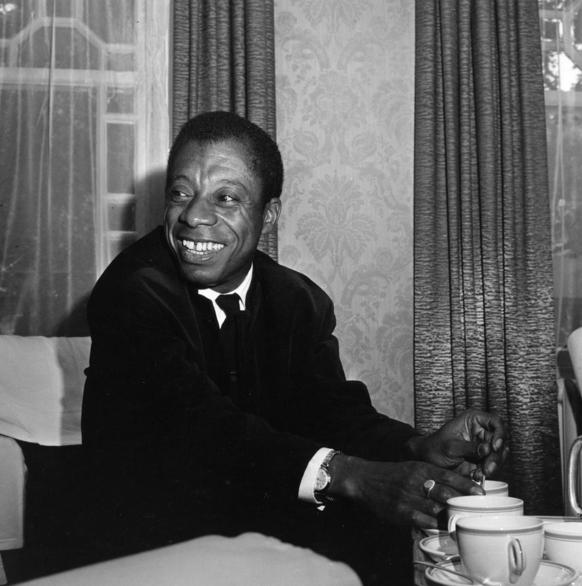 Gap-Toothed Grinners: American writer and Civil Rights activist James Baldwin (1924 - 1987) at the Whitehall Hotel, Bloomsbury Square, London.   (Photo by Jenkins/Getty Images)