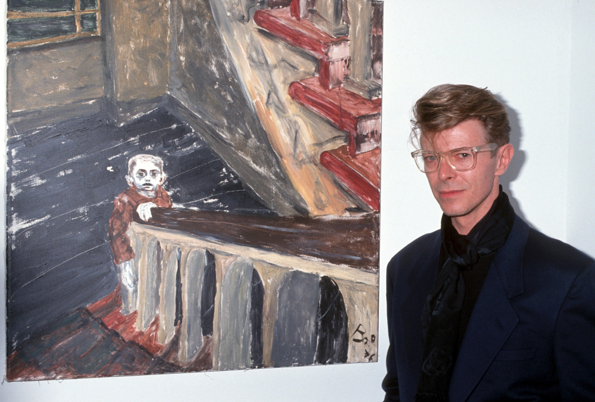 David Bowie: A musician, actor and artist, David Bowie stands next to one of his paintings at a New York gallery show in 1990. (Photo by Ron Galella/WireImage)
