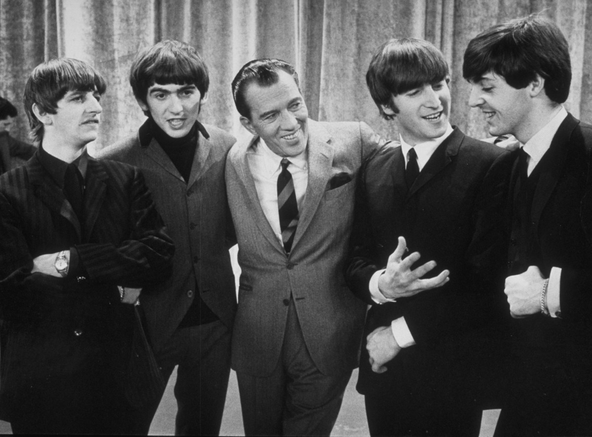 American television host Ed Sullivan smiles while standing with British rock group the Beatles on the set of his television variety series, New York, February 9, 1964. Left to right: Ringo Starr, George Harrison, Sullivan, John Lennon, Paul McCartney. (Photo by Express Newspapers/Getty Images)