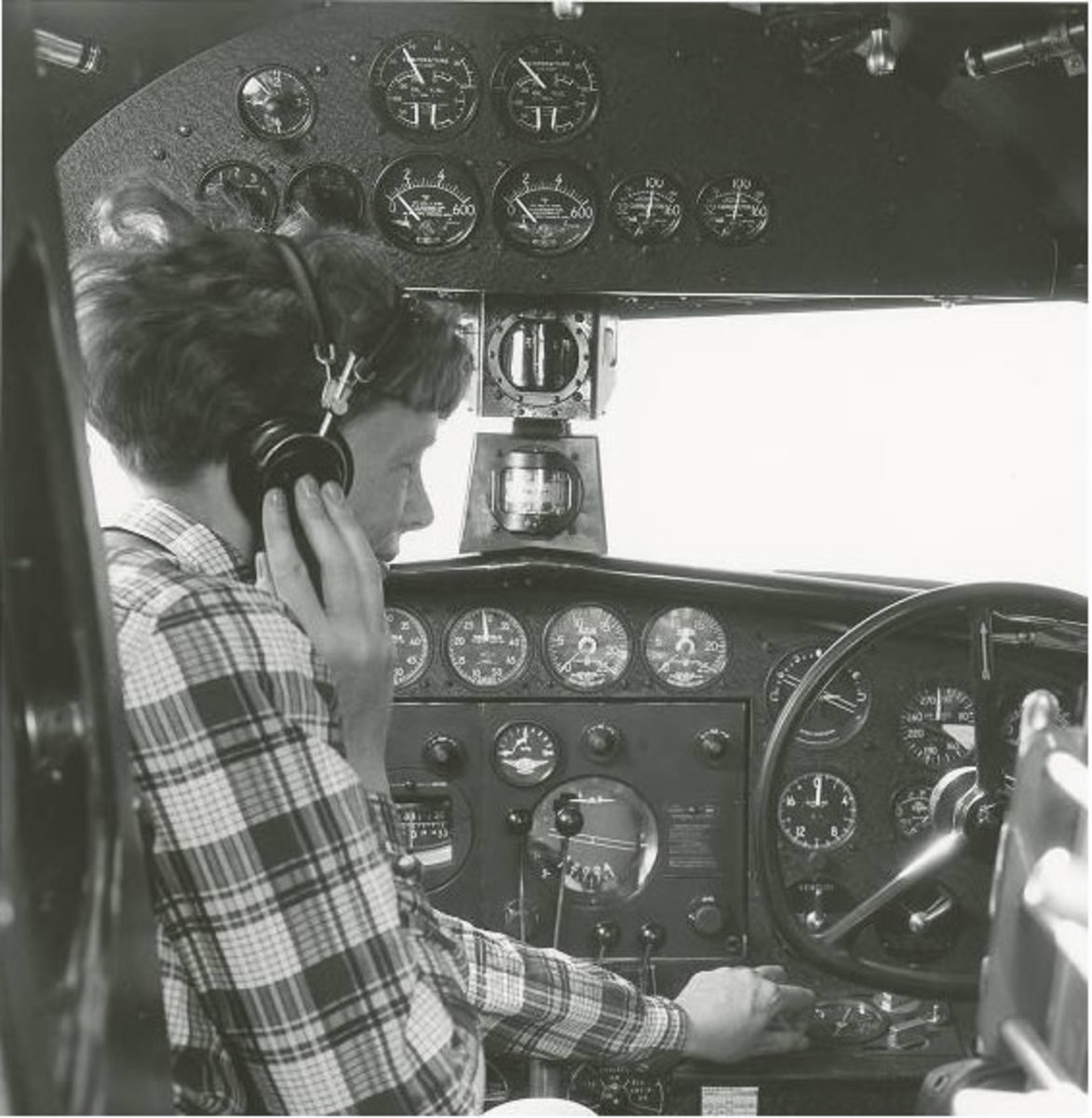 Amelia Earhart: Amelia Earhart with headphones adjusting the controls in the cockpit of her Lockheed Electra. George Palmer Putnam Collection of Amelia Earhart Papers, Courtesy of Purdue University Libraries, Karnes Archives and Special Collections.