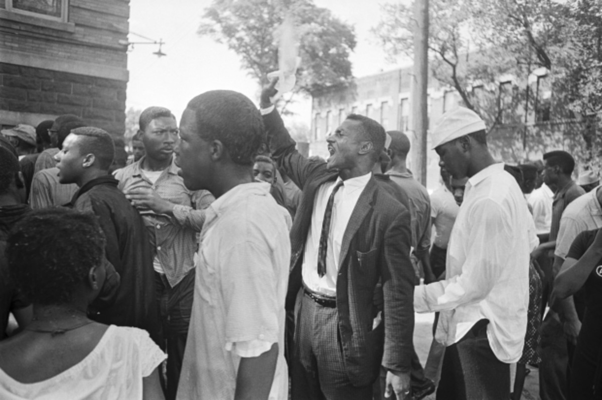 Reverend Fred Shuttlesworth rallies a group of people at a segregation protest after they were attacked by people throwing rocks and bottles. May 8, 1963. Birmingham, AL (Corbis)