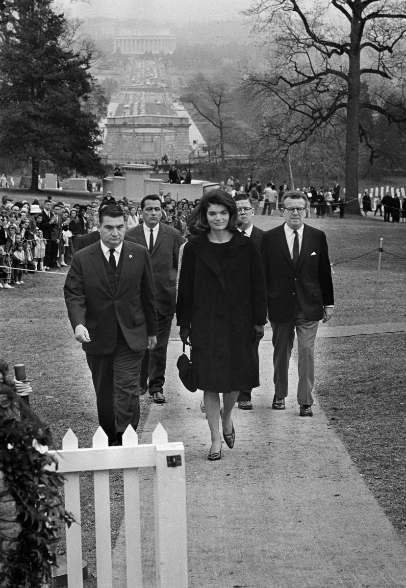 Jacqueline Kennedy walks to the grave of her slain husband, President John F. Kennedy, in Arlington National Cemetery, Arlington, Va., Nov. 28, 1963. Others, from left, are: Pierre Salinger, White House press secretary; Secret Service agent Clinton J. Hill; and presidential aides Jack McNall and Lawrence O'Brien. Ropes keep ordinary mourners at a distance on the hillside overlooking Memorial Bridge to Washington and the Lincoln Memorial in background.   (AP Photo/Bob Schutz)