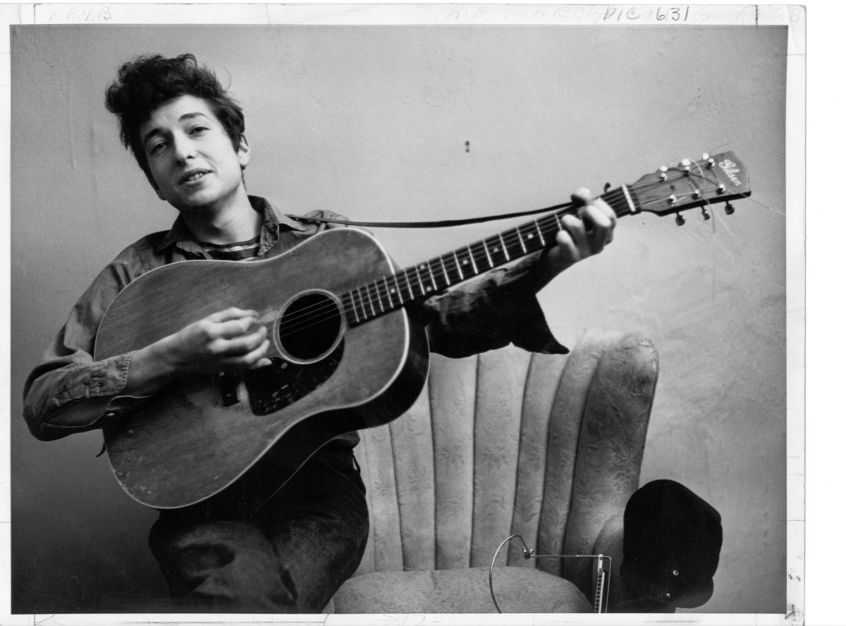 Bob Dylan: With his Gibson Acoustic guitar around him, Dylan lets loose in this portrait. NYC, 1961.