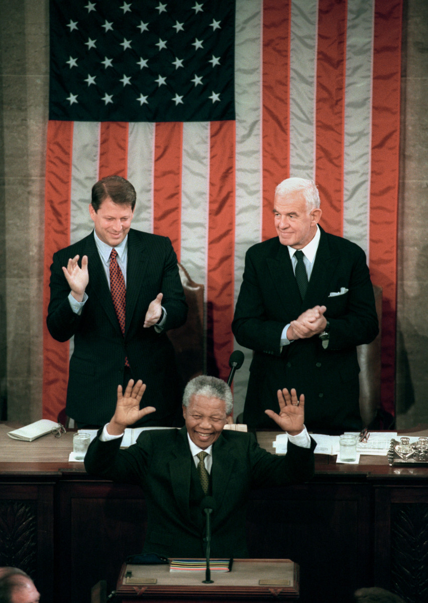 U.S. Vice President Al Gore (L) and Speaker of the House Tom Foley (R) join the audience as they cheer for South African President Nelson Mandela while he delivers remarks to a joint meeting of Congress in Washington DC, on October 6, 1994.