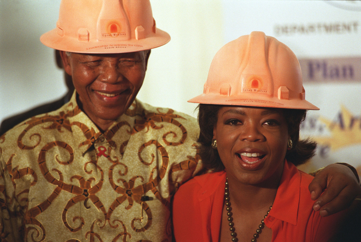 Nelson Mandela Photo Gallery: Nelson Mandela and Oprah Winfrey don matching construction hard hats to break the ground for her $10 million Leadership Academy for Girls in South Africa in 2002. She described Mandela as her 'hero' and he called her a 'queen.' (Photo courtesy of Getty Images)