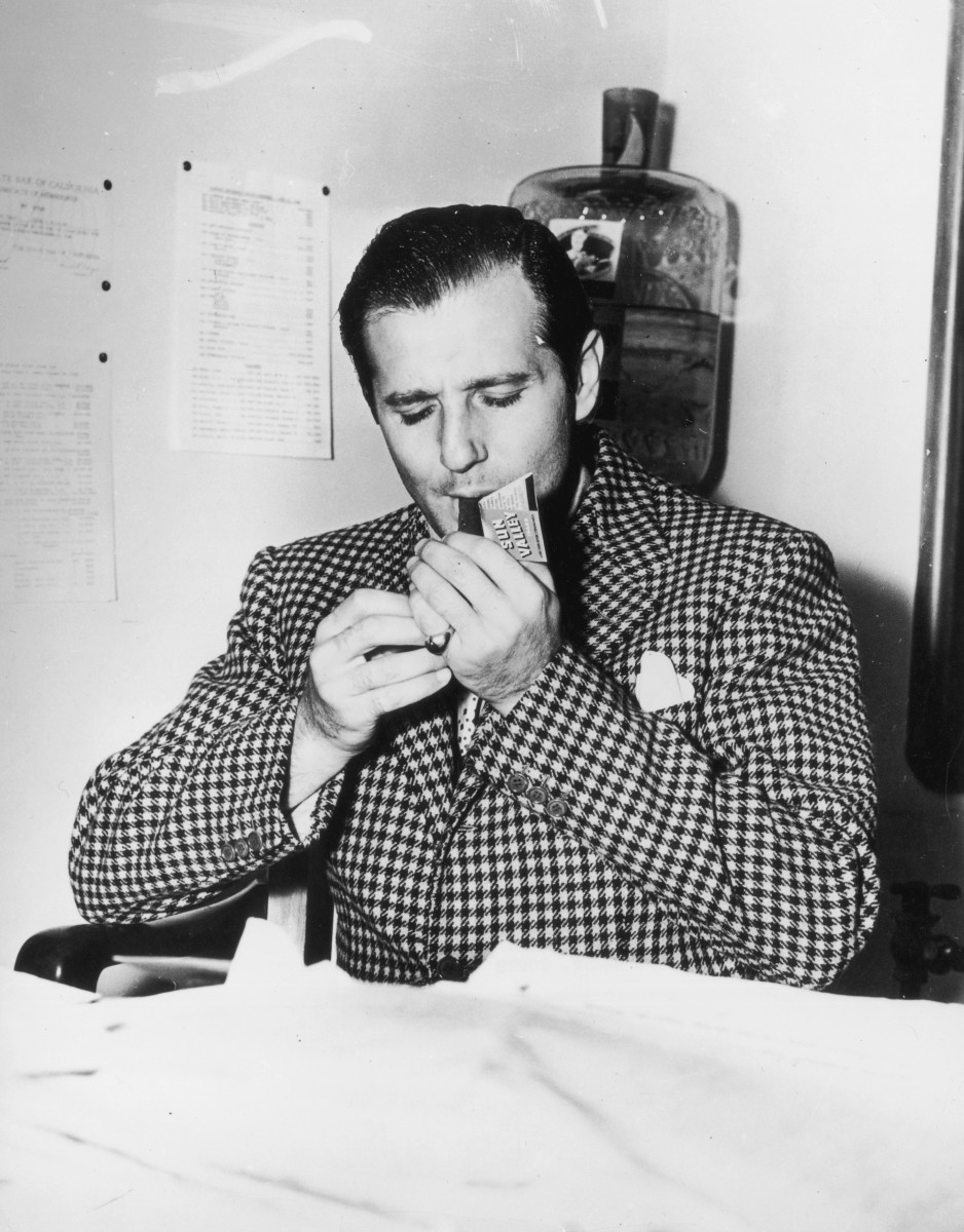 "Infamous Mobsters: The well-tailored, Brooklyn-born Benjamin ""Bugsy"" Siegel lights a cigar in 1940. Bugsy was a gambler, bootlegger and known affiliate of the Genovese crime family."