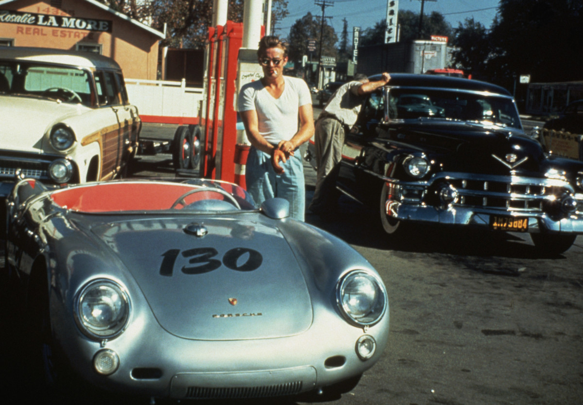 Celebrities and Their Fast Cars: Just hours before his crash, James Dean takes a cigarette break at a gas station next to his beloved silver Porsche 550 Spyder that he named Little Bastard.